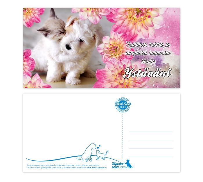 Koira, kissa ja eläinaiheinen Ystävänpäiväkortti. Kissa halaa koiran pentua. Kuvassa myös pinkin värisiä daalian kukkia ja teksti: Sylillinen kukkia ja lämpöisiä halauksia sinulle Ystäväni.
